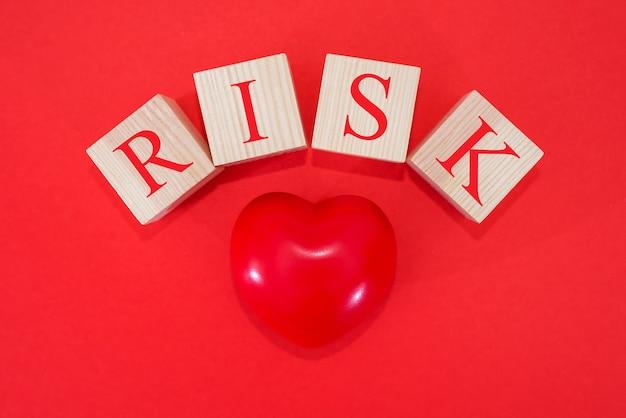 Cuore rosso e la parola rischio su cubi di legno su sfondo rosso. malattie cardiache, concetto di diabete
