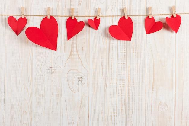 Cuori rossi sono tenuti da mollette su corda di iuta, su legno bianco. copia spazio