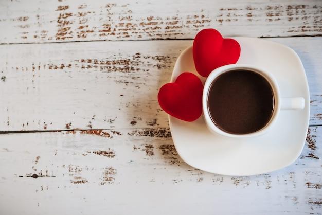Cuori rossi e una tazza di caffè su un fondo di legno bianco