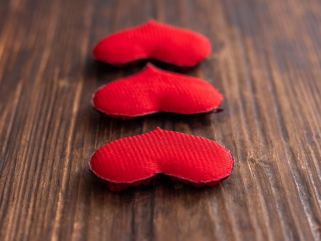 Cuori rossi su uno sfondo di legno scuro, un'immagine per le congratulazioni di san valentino