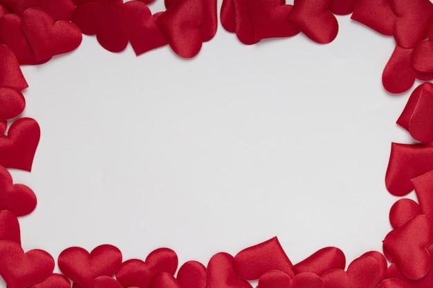 Cornice cuori rossi con sfondo bianco, giorno di san valentino e concetto di amore