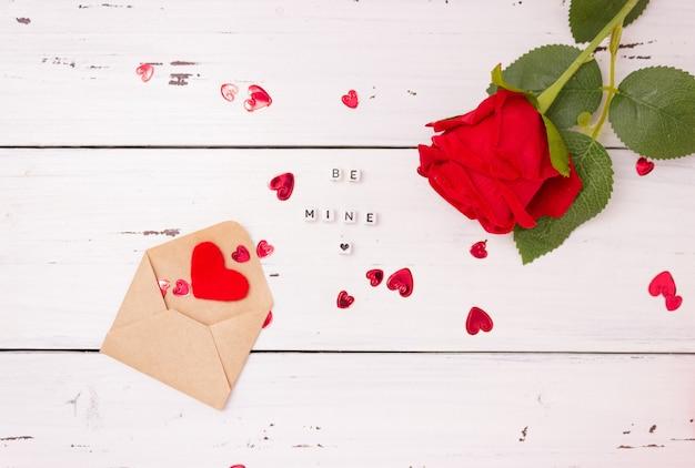 Cuori rossi, busta da lettera aperta in carta kraft e una rosa