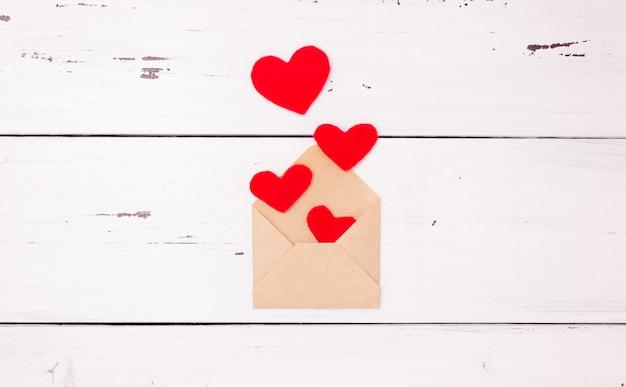 Cuori rossi e una busta per lettere aperta fatta di carta kraft
