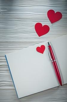 Taccuino della penna dei cuori rossi sul concetto di istruzione del bordo di legno