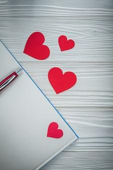 Blocco note della penna dei cuori rossi sul concetto di istruzione del bordo di legno