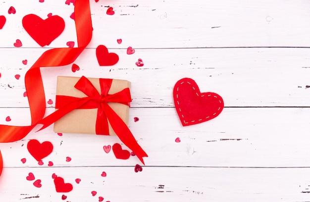Cuori, nastro e regalo rossi su fondo di legno bianco. vista dall'alto, spazio libero per il testo. san valentino, amore.