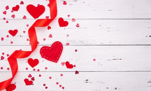 Cuori e nastro rossi su un fondo di legno bianco. vista dall'alto, spazio libero per il testo. san valentino, amore.