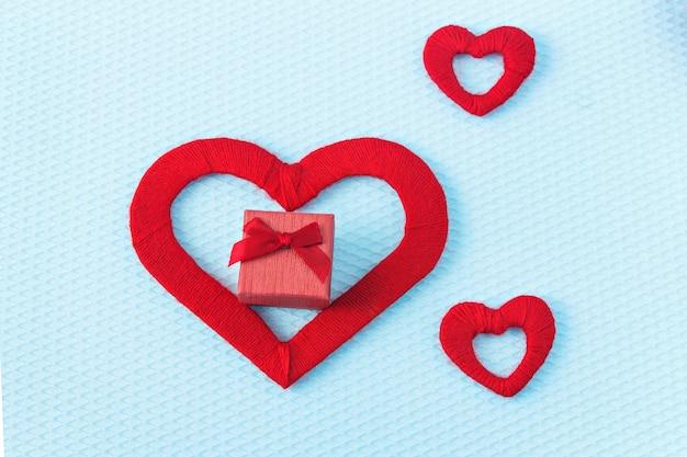 Cuori rossi e anello su sfondo blu