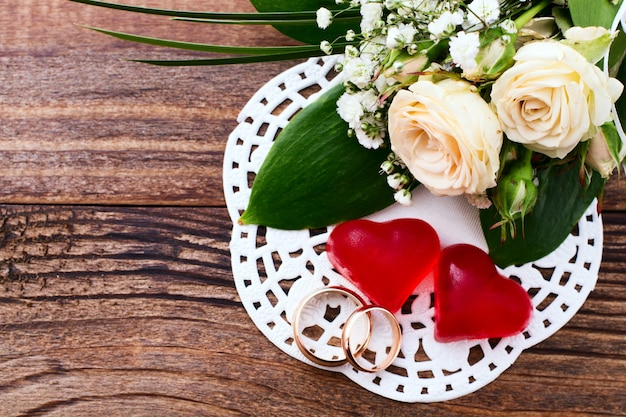 Cuori rossi, fedi nuziali e fiori sullo scrittorio di legno.