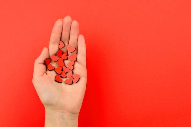 Cuori rossi in mano di donna su sfondo rosso copia spazio