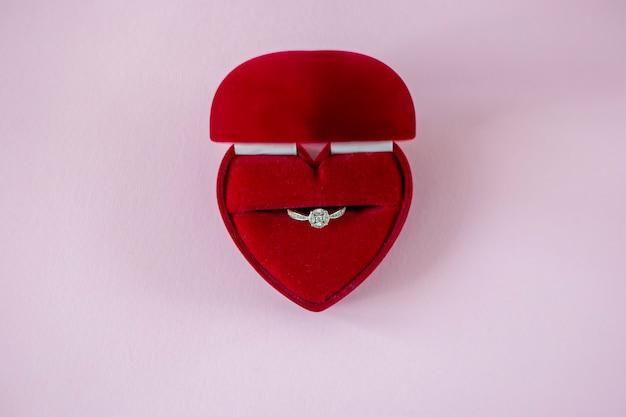 Scatola rossa a forma di cuore con anello di fidanzamento su sfondo rosa