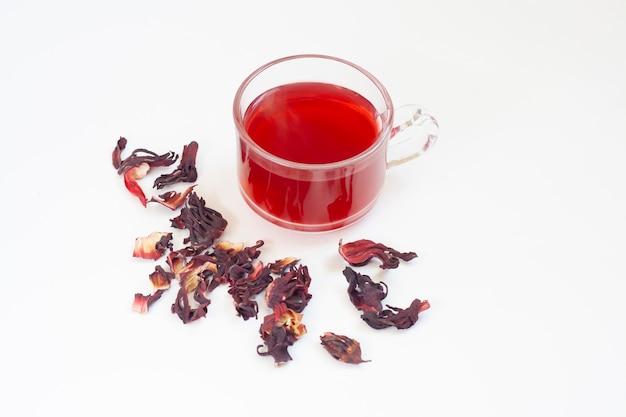 Tè di ibisco rosso in una tazza e fiori di ibisco essiccati