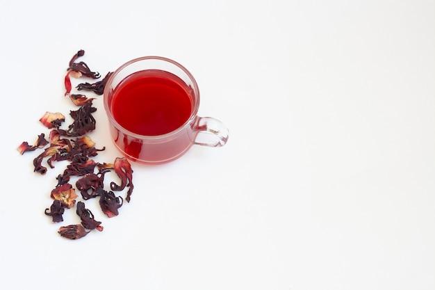 Tè di ibisco rosso in una tazza di vetro trasparente e fiori di ibisco essiccati