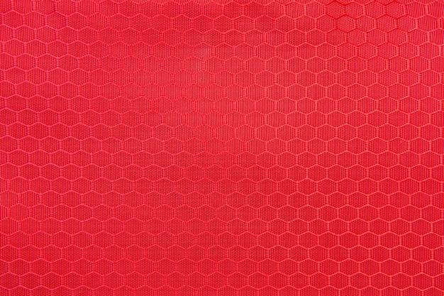 Trama di sfondo rosso a nido d'ape. sfondo texture di tessuto in poliestere. modello in tessuto a trama plastica