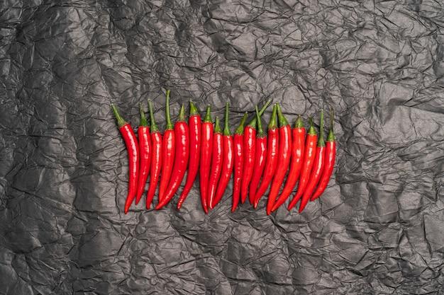 Peperoncini rossi roventi in fila su un nero