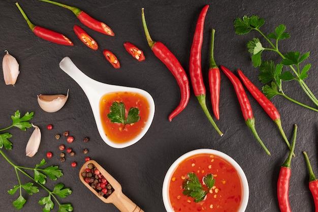Salsa al peperoncino rosso. ketchup, salsa al peperoncino, purea di peperoncino, verdure, pomodori e aglio. sulla superficie di pietra nera. vista dall'alto