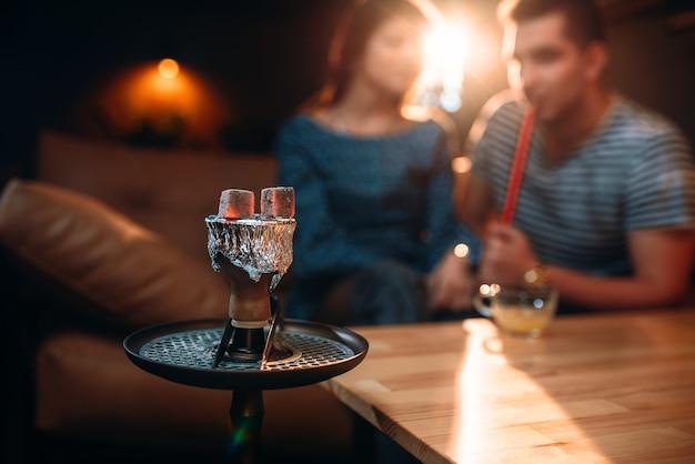 Carbone rovente sul narghilè nel night club. giovane coppia fuma tabacco, fumo e relax notturno