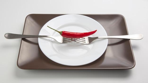 Peperoncino rosso sulla forcella sul piatto in ceramica. spezie e cibo vegetativo