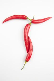 Peperoncino rosso su sfondo bianco a forma di lettera t. utile cibo vegetale e vitamine