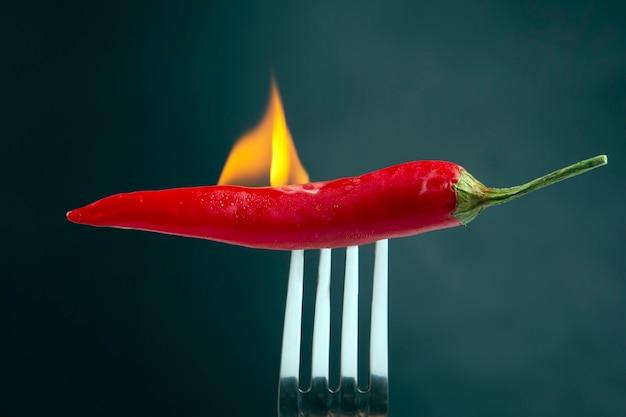 Peperoni roventi su una forchetta nel fuoco reale