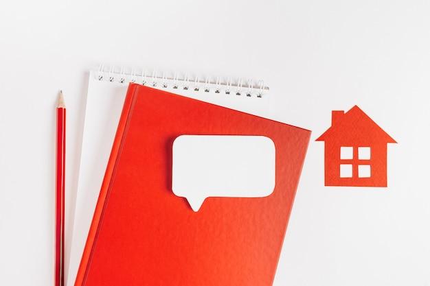 Casa rossa, blocco note e adesivo nello spazio della copia