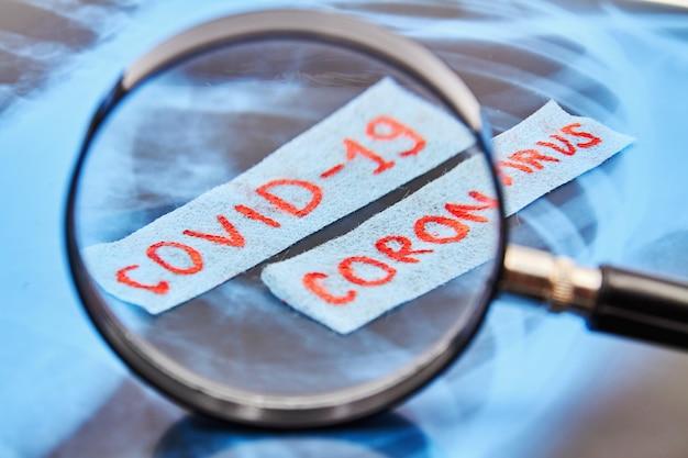 Iscrizione rossa covid-19 coronavirus attraverso una lente d'ingrandimento su radiografia polmonare di sfondo. concetto di protezione dal coronavirus. primo piano, messa a fuoco selettiva