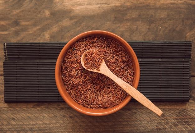 Ciotola rossa dei grani del riso del gelsomino contro il contesto di legno