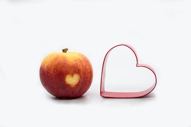Mela rossa succosa con un ritaglio a forma di cuore e un tagliabiscotti a forma di cuore