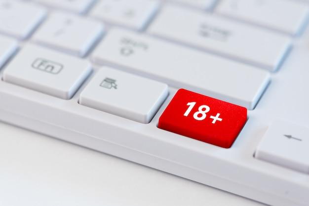 Tasto rosso con 18+ simbolo di concetto sulla tastiera del laptop