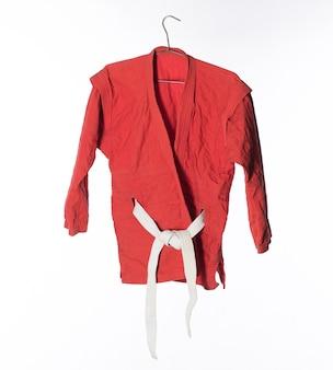 Kimono rosso per arti marziali isolato su sfondo bianco