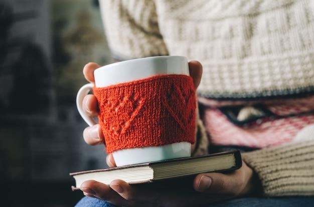 Tazza di lana lavorata a maglia rossa con motivo a cuore in mani femminili.