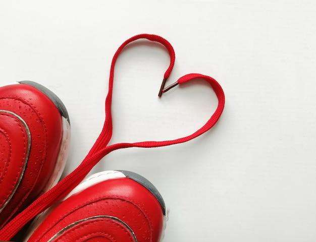Cuore di pizzo rosso, segno d'amore, scarpe sportive rosse su sfondo bianco, primo piano di messa a fuoco selettiva