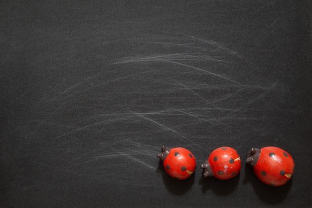 Giocattoli rossi delle coccinelle sulla lavagna nera con lo spazio in bianco della copia