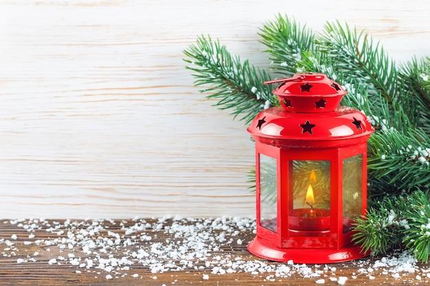 Lanterna rossa con una candela accesa e decorazioni di capodanno sulla neve e sullo sfondo di legno bianco