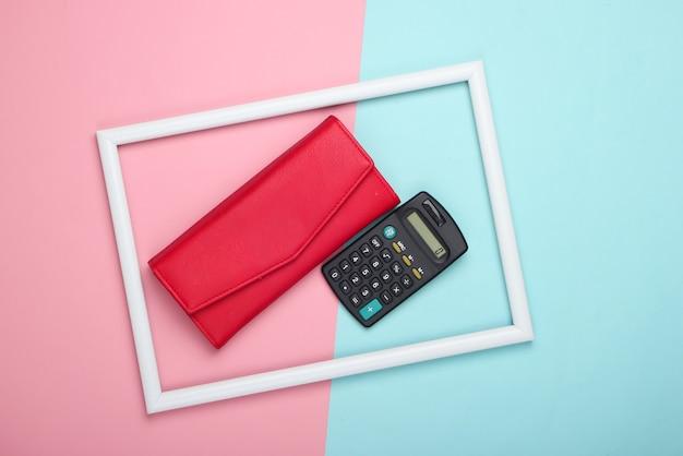 Portafoglio in pelle rossa e calcolatrice in cornice bianca su superficie pastello blu rosa