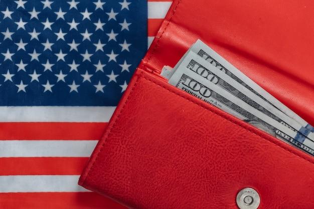 Portafoglio in pelle rossa con banconote da cento dollari sulla bandiera degli stati uniti