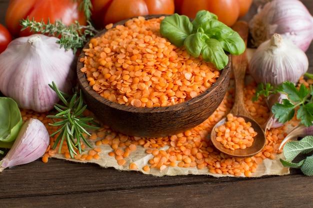 Lenticchie rosse in una ciotola con pomodori, aglio ed erbe aromatiche su legno