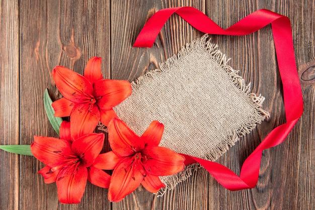 I gigli rossi fioriscono su legno scuro