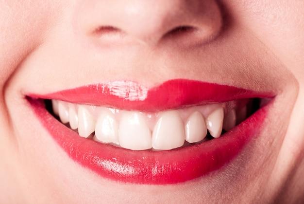 Primo piano di sorriso di labbra rosse con denti bianchi