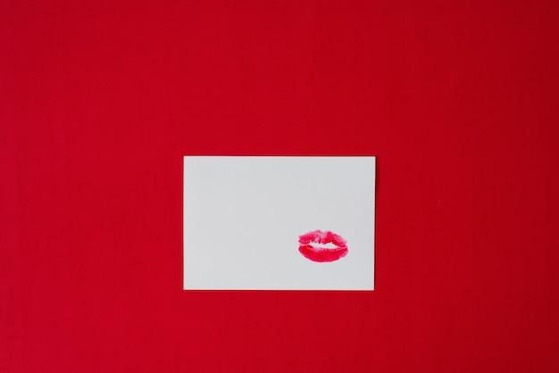 Stampa del labbro rossetto rosso bacio sul foglio di carta bianco su sfondo rosso