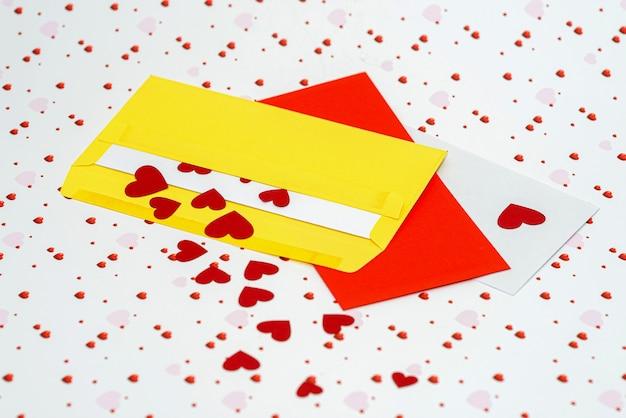 Cuoricini rossi che escono dalla busta sullo sfondo del giorno di san valentino con spazio di copia, concetto di lettera d'amore, primo piano