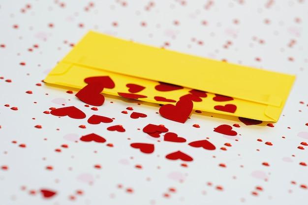 Cuoricini rossi che escono dalla busta gialla sullo sfondo del giorno di san valentino con spazio di copia, concetto di lettera d'amore, primo piano