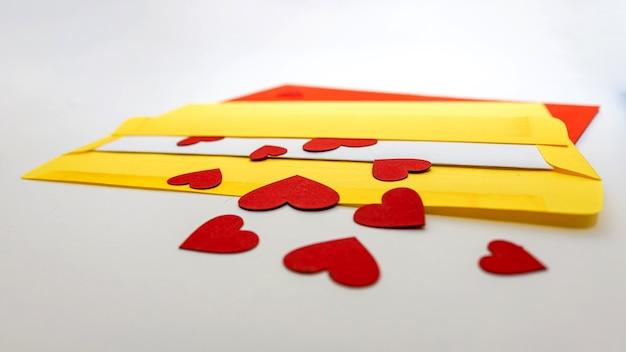 Piccoli cuori rossi che escono dalla busta gialla su fondo bianco con lo spazio della copia, concetto di lovelette, primo piano