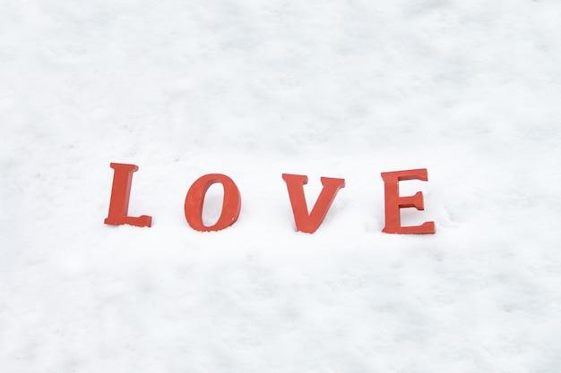 Lettere d'amore rosse sulla neve bianca. parola amore su sfondo bianco giorno di amici o amanti di san valentino