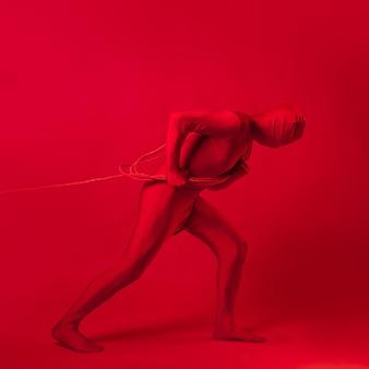 L'uomo rosso trascina qualcosa su una corda un concetto di lavoro e ansia