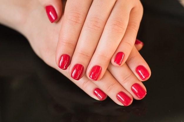 Manicure rossa con unghie su una superficie nera