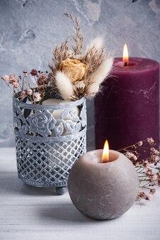 Il marsala rosso ha acceso le candele e il mazzo di fiori secchi in vaso di latta sulla tavola di legno bianca.