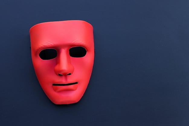 Maschera rossa sul tavolo scuro.