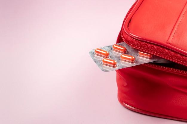 Scatola rossa della medicina con blister che esce e spazio per il testo.