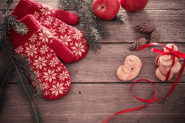 Guanti rossi e decorazioni natalizie su fondo in legno